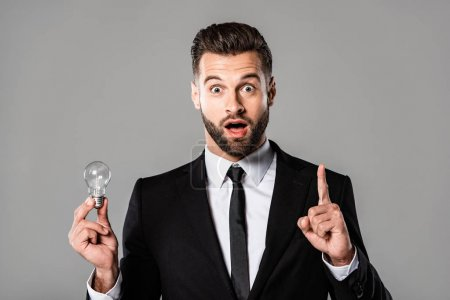 Photo for Shocked businessman in black suit holding light bulb and showing idea gesture isolated on grey - Royalty Free Image