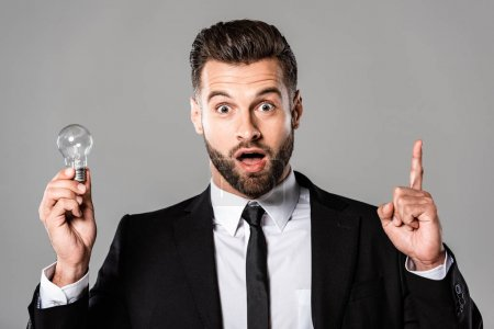 Photo for Surprised businessman in black suit holding light bulb and showing idea gesture isolated on grey - Royalty Free Image