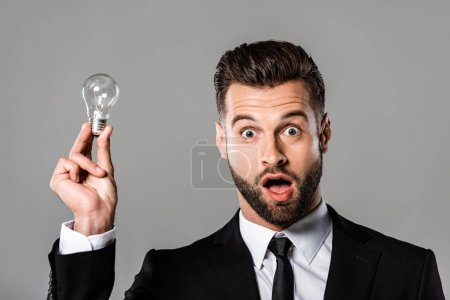 Photo for Shocked businessman in black suit holding light bulb isolated on grey - Royalty Free Image