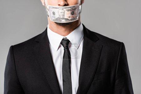 Photo pour Vue recadrée de l'homme d'affaires dans le procès noir avec le billet de banque de dollar sur la bouche d'isolement sur le gris - image libre de droit