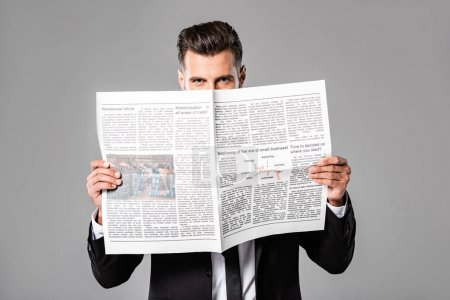 businessman in black suit with newspaper isolated on grey