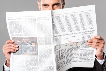 handsome businessman in black suit with newspaper isolated on grey