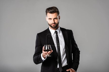 Photo for Handsome businessman in black suit holding glass with whiskey isolated on grey - Royalty Free Image