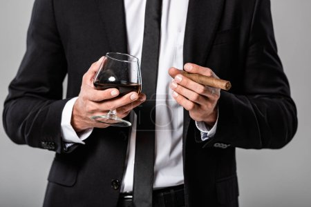 Photo for Partial view of businessman in black suit holding glass with whiskey and cigar isolated on grey - Royalty Free Image