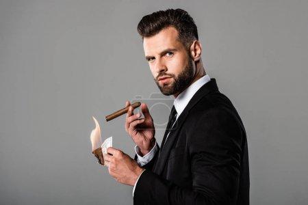 Photo pour Vue de côté de l'homme d'affaires riche dans le procès noir illuminant le cigare du billet de banque de dollar brûlant d'isolement sur le gris - image libre de droit