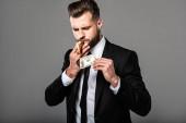 """Постер, картина, фотообои """"богатый бизнесмен освещает сигару от горящей долларовой банкноты изолированы на серый"""""""