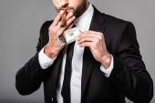"""Постер, картина, фотообои """"частичный вид богатого успешного бизнесмена в черном костюме, освещающего сигару от горящей долларовой банкноты, изолированной на сером"""""""