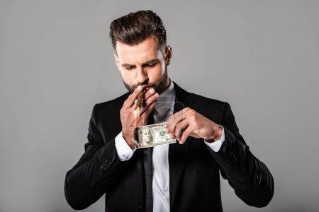 Photo pour Riche homme d'affaires réussi dans le costume noir allumant le cigare du dollar brûlant isolé sur le gris - image libre de droit