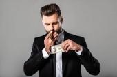 """Постер, картина, фотообои """"богатый успешный бизнесмен в черном костюме освещает сигару от горящего доллара изолированы на серый"""""""