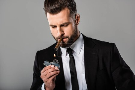 Photo for Handsome businessman in black suit lighting up cigar isolated on grey - Royalty Free Image
