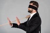 """Постер, картина, фотообои """"side view of blindfolded businessman in black suit with noose on neck showing stop gesture isolated on grey"""""""