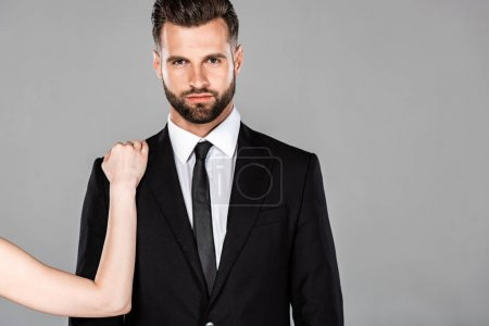 Photo for Woman touching successful businessman in black suit isolated on grey - Royalty Free Image