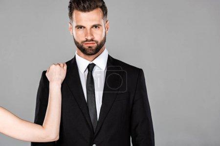 Photo pour Femme touchant homme d'affaires réussi en costume noir isolé sur gris - image libre de droit
