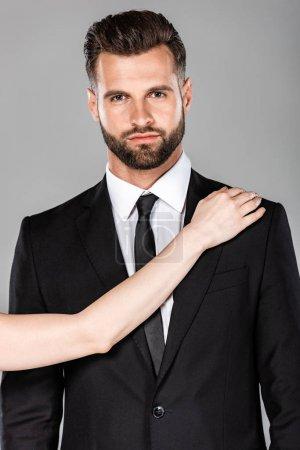 Photo pour Femme touchant l'épaule de l'homme d'affaires réussi dans le procès noir d'isolement sur le gris - image libre de droit