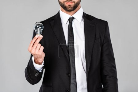 Photo for Partial view of successful businessman in black suit holding light bulb isolated on grey - Royalty Free Image