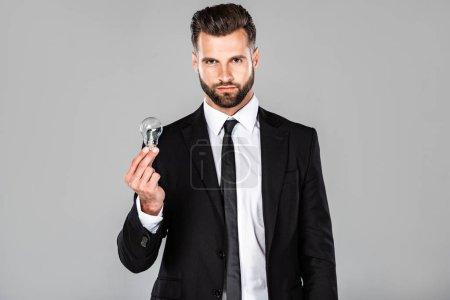 Photo pour Beau homme d'affaires réussi dans le costume noir retenant l'ampoule d'ampoule d'isolement sur le gris - image libre de droit