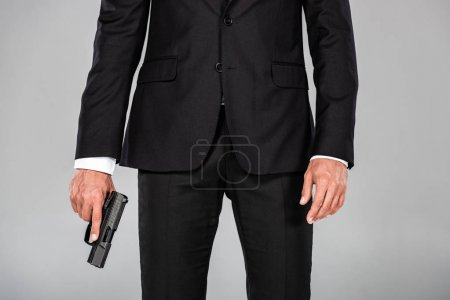 Photo for Partial view of agent in black suit with gun isolated on grey - Royalty Free Image
