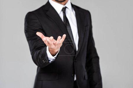 Photo pour Vue partielle de l'homme d'affaires dans le procès noir avec la main de mendicité d'isolement sur le gris - image libre de droit