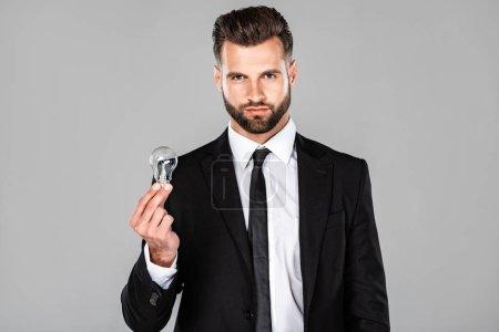 Photo pour Homme d'affaires réussi dans le procès noir retenant l'ampoule d'ampoule d'isolement sur le gris - image libre de droit