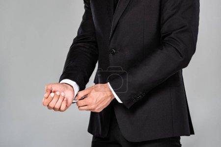 Photo pour Vue recadrée de l'homme d'affaires élégant en costume noir bouton de fermeture sur chemise isolée sur gris - image libre de droit