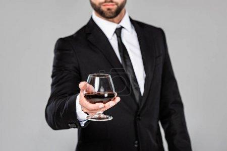 Photo pour Vue recadrée de l'homme d'affaires réussi dans le verre noir de fixation de costume avec le whiskey d'isolement sur le gris - image libre de droit