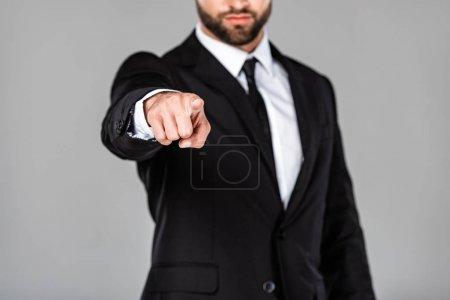 Photo pour Vue recadrée de l'homme d'affaires en costume noir pointant du doigt la caméra isolée sur gris - image libre de droit