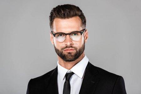 Photo pour Portrait d'homme d'affaires réussi dans le costume noir et les glaces d'isolement sur le gris - image libre de droit
