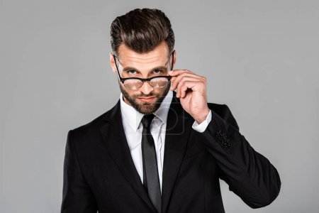 confident successful businessman in black suit and glasses isolated on grey