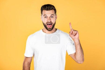 Photo pour Homme beau excité dans le t-shirt blanc affichant le geste d'idée d'isolement sur le jaune - image libre de droit