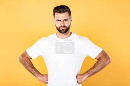 lächelnder gutaussehender Mann im weißen T-Shirt mit den Händen an den Hüften vereinzelt auf gelb