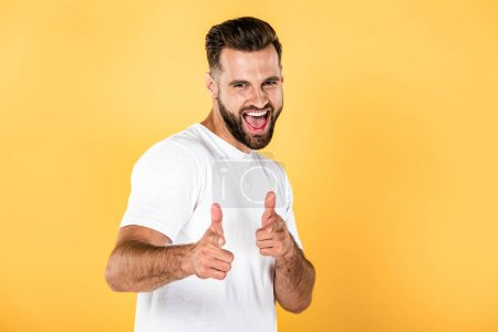 Photo for Happy handsome man in white t-shirt pointing with fingers at camera isolated on yellow - Royalty Free Image