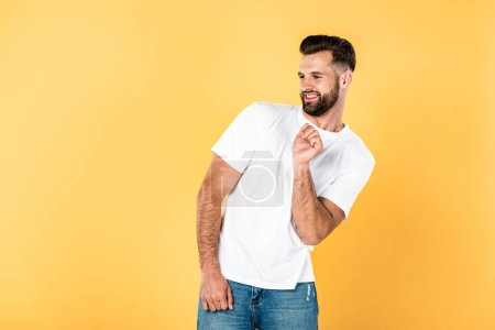Photo for Cheerful handsome man in white t-shirt dancing isolated on yellow - Royalty Free Image