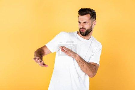 Photo pour Bel homme en t-shirt blanc geste avec les mains isolées sur jaune - image libre de droit