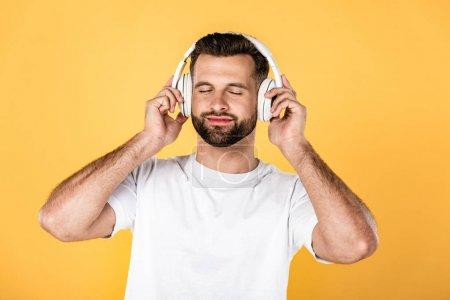 Photo pour Heureux bel homme en t-shirt blanc écouter de la musique dans les écouteurs avec les yeux fermés isolé sur jaune - image libre de droit