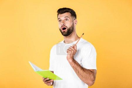 Photo pour Homme beau choqué en t-shirt blanc avec crayon à bouche ouverte et bloc-notes isolé sur jaune - image libre de droit