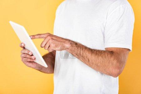 Photo pour Vue partielle de l'homme en t-shirt blanc en utilisant une tablette numérique isolée sur jaune - image libre de droit