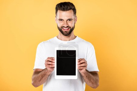 happy man in white t-shirt showing digital tablet with blank screen isolated on yellow