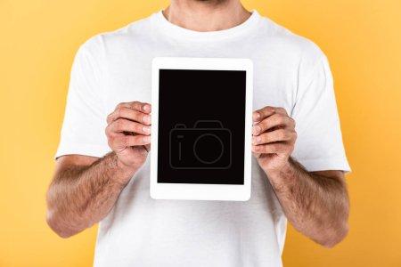 vue recadrée de l'homme en t-shirt blanc montrant tablette numérique avec écran blanc isolé sur jaune