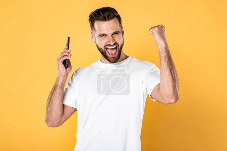 Photo for Happy man in white t-shirt talking on smartphone and showing yes gesture isolated on yellow - Royalty Free Image
