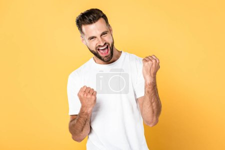 Photo for Happy man in white t-shirt showing winner gesture isolated on yellow - Royalty Free Image