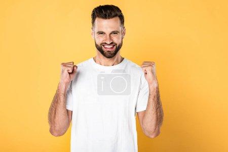 Photo pour Homme excité dans le t-shirt blanc affichant le geste de oui isolé sur le jaune - image libre de droit