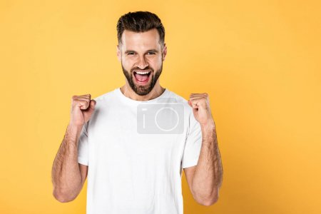 Photo for Excited man in white t-shirt showing yes gesture and screaming isolated on yellow - Royalty Free Image