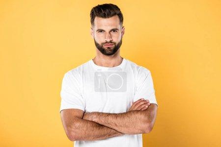 Foto de Hombre guapo en camiseta blanca con los brazos cruzados aislados en amarillo - Imagen libre de derechos