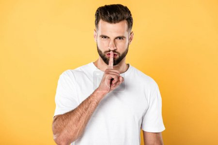 Photo for Handsome man in white t-shirt showing shh sign isolated on yellow - Royalty Free Image