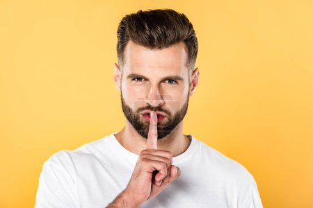 handsome man in white t-shirt showing hush sign isolated on yellow