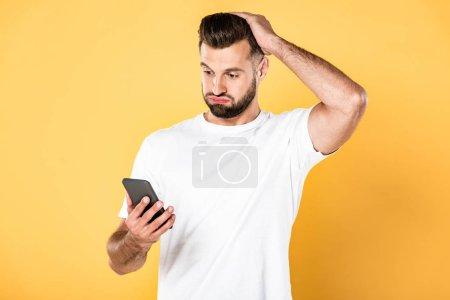 Photo pour Confus bel homme en t-shirt blanc en utilisant smartphone isolé sur jaune - image libre de droit