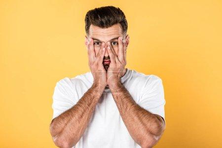 Photo pour Homme beau drôle dans le t-shirt blanc avec des mains sur le visage d'isolement sur le jaune - image libre de droit