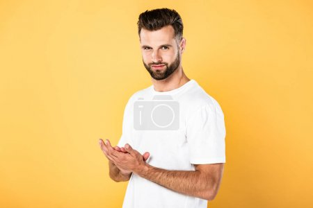 Photo for Handsome man in white t-shirt rubbing his hands isolated on yellow - Royalty Free Image