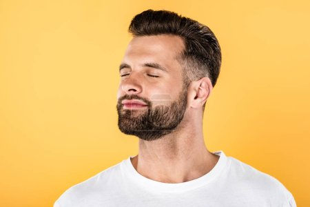 Photo for Joyful handsome man in white t-shirt with closed eyes isolated on yellow - Royalty Free Image
