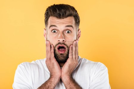Photo for Scared handsome man in white t-shirt with open mouth isolated on yellow - Royalty Free Image